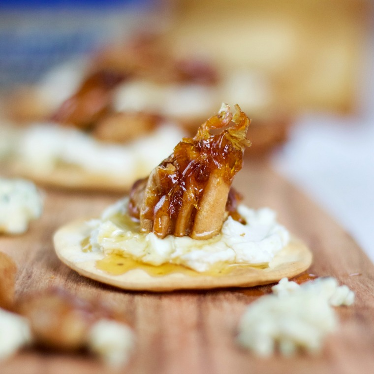 close up photo of a shiny candied pecan on a cracker with a blue cheese spread