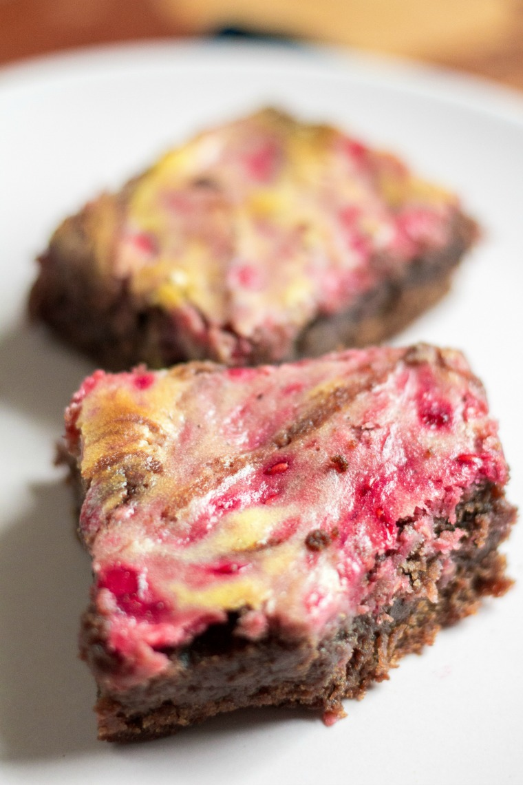 a close up of one cheesecake brownie, with another in the background