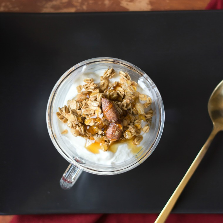 yogurt with granola on top in a cup on a black plate
