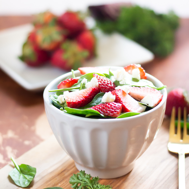 a spinach salad containing feta and strawberries in a small white bowl