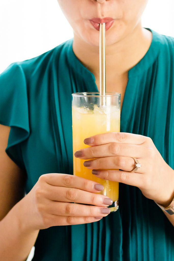 a female holding a glass of punch and sipping it through a straw