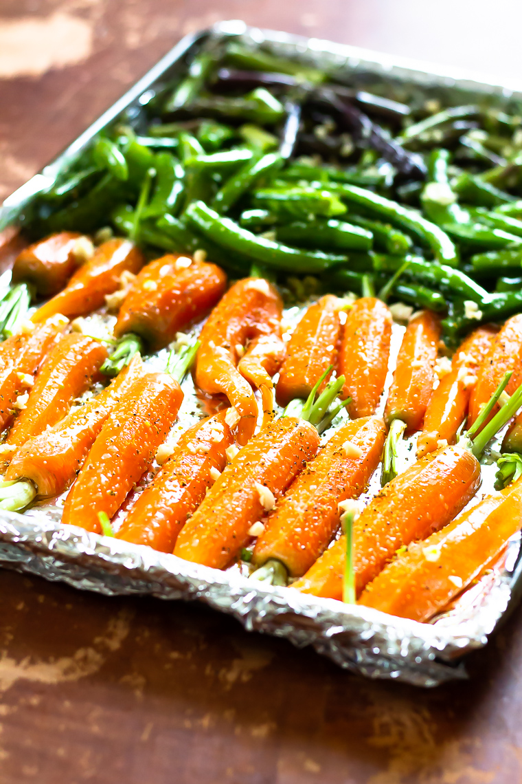 side view of a pan of vegetables, primarily carrots, ready to go into the oven.