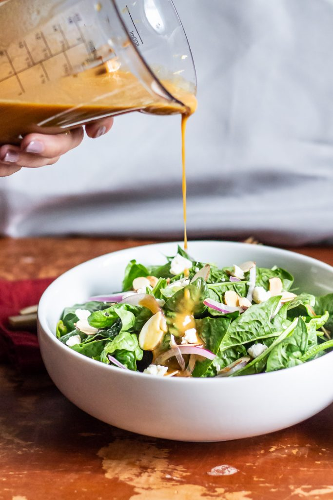 pouring peanut dressing onto a spinach salad topped with onions and almonds