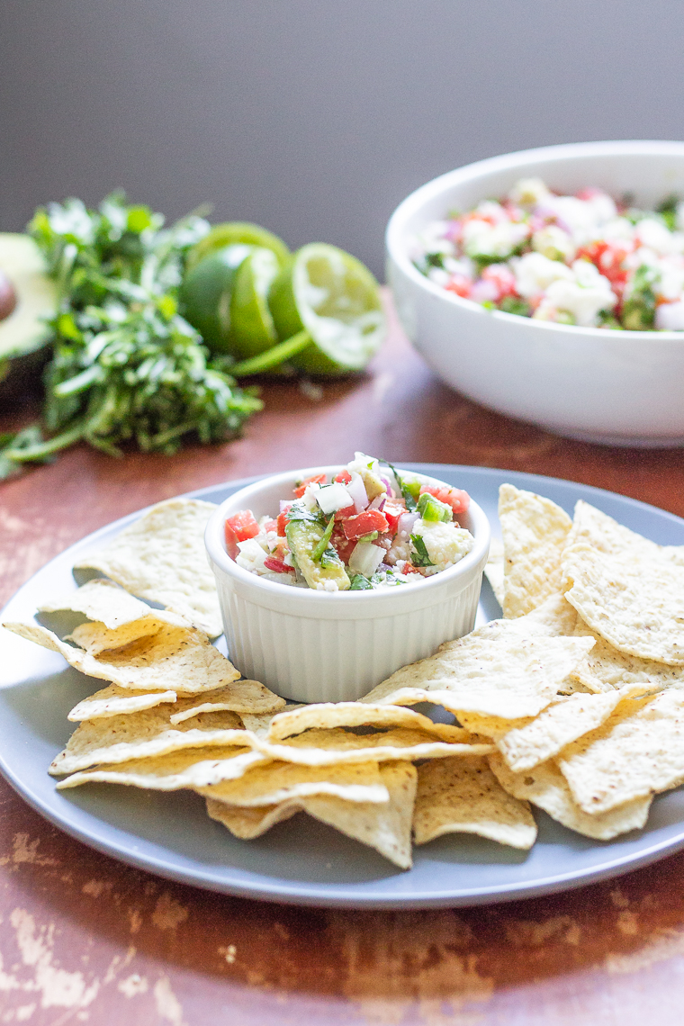 a ramekin of avocado salsa surrounded by tortilla chips for dipping
