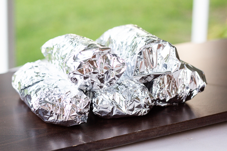 five burritos wrapped in foil stacked together in a pile
