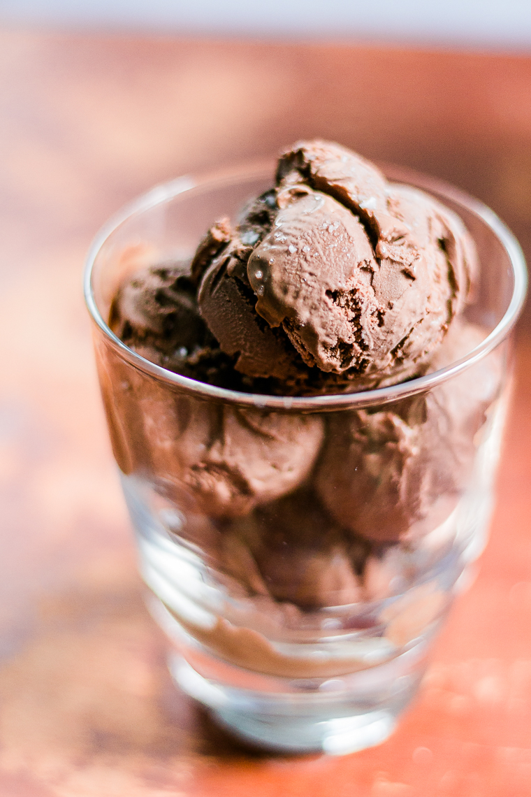 side view of a cup containing chocolate ice cream with flaked salt on top