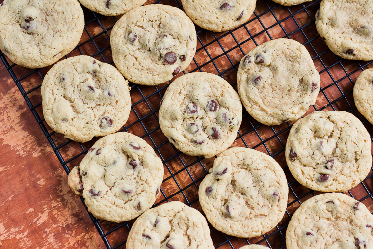 a wire rack filled with chocolate chip cookies
