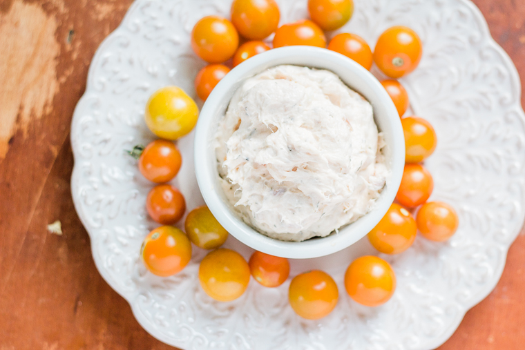 overhead shot of smoked salmon dip in a bowl and cherry tomatoes on a plate.