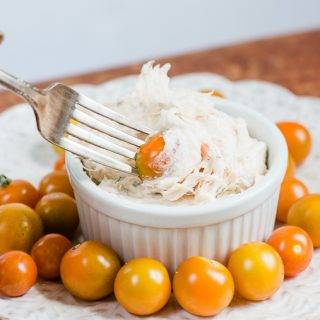 smoked salmon dip being dipped into by a fork with a cherry tomato on it