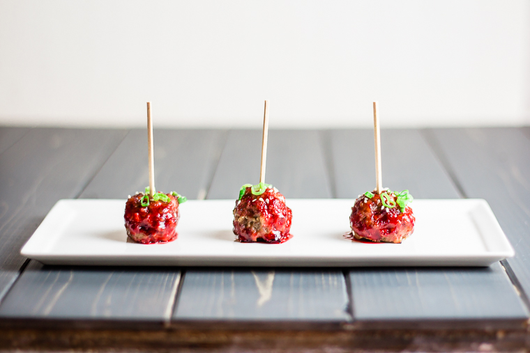 a row of three cocktail meatballs on a plate covered in cranberry sauce and garnished with green onions and sesame seeds