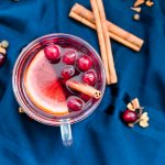 overhead view of a cup of mulled wine with cranberries, cinnamon stick and orange floating on top, over a blue napkin background with some scattered ingredients on the napkin