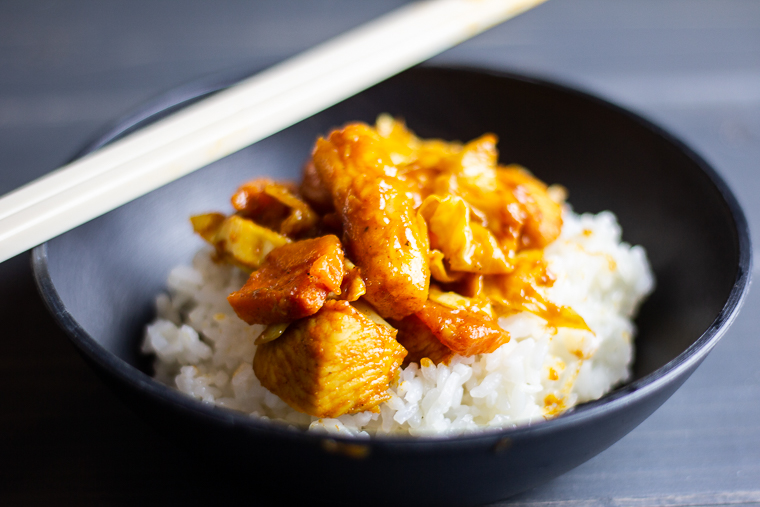 a side view of dakgalbi heaped on a bed of white rice in a black bowl.