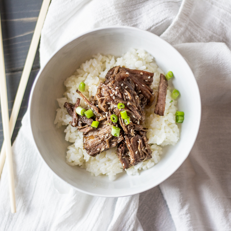 an overhead shot of a bowl of korean style pot roast garnished with sesame seeds and green onions on a bed of white rice