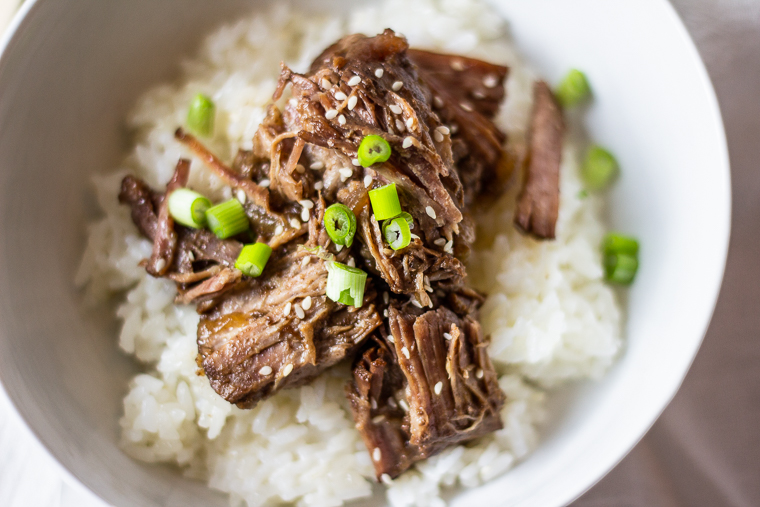 a close up of a bowl of korean style potroast garnished with sesame seeds and green onions on a bed or white rice