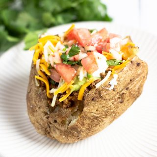 a baked potato topped with taco toppings
