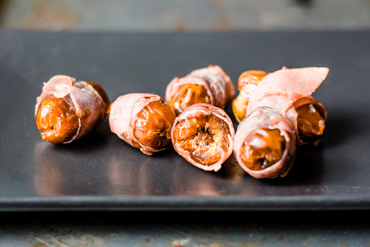 a group of mexican chocolate prosciutto wrapped dates on a rectangular plate, one with a bite out of it revealing the chocolate inside