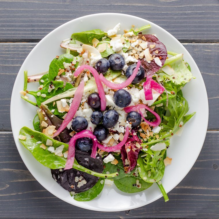 overhead shot of a white plate filled with quinoa and salad topped with pickled red onions, blueberries, feta cheese, and toasted coconut.