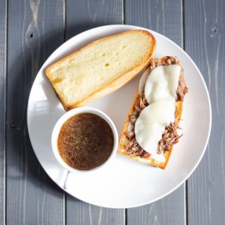 an overhead shot of an open faced french dip sandwich with melted provolone cheese on top next to a cup of au jus and the top piece of bread