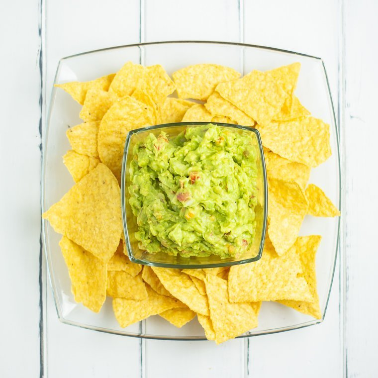 an over head shot of a clear bowl full of guacamole sitting on top of a clear glass plate with yellow corn chips surrounding the bowl of chips