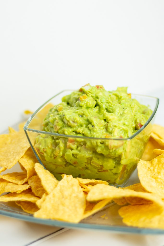 a clear bowl full of guacamole sitting on top of a clear glass plate with yellow corn chips surrounding the bowl of chips