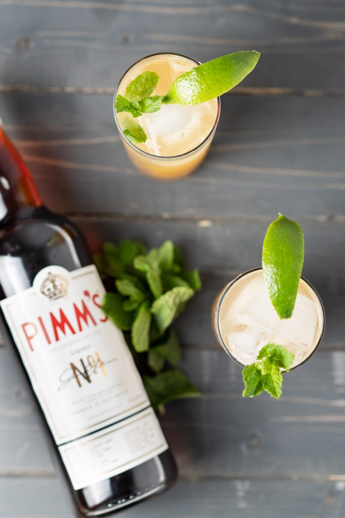 overhead shot of a bottle of pimm's no.1, and two glasses with cocktails in them