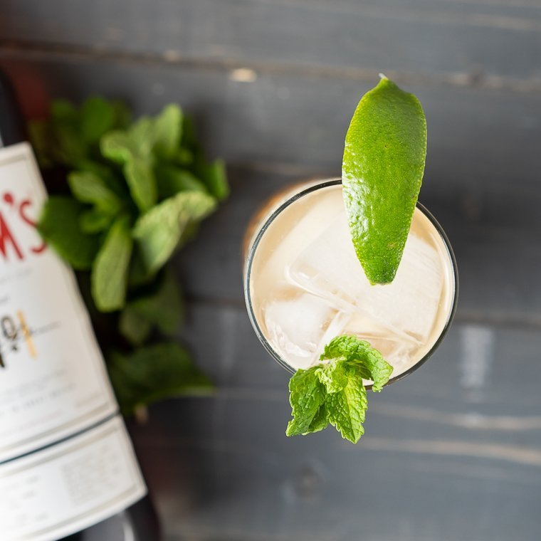 a top view of a cup with a cocktail with ice inside, garnished with a sprig of mint and a lime wedge