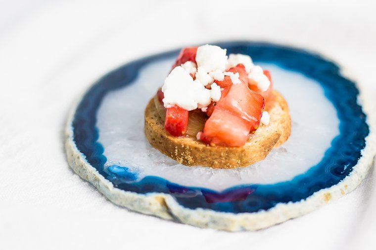 a slice of strawberry bruschetta sitting on a slide of geode