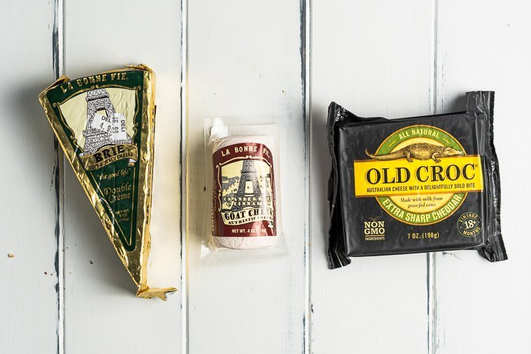 three cheeses in their packaging against a white wooden backdrop