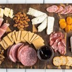 a wooden board with a lot of different foods on it - crackers, meats, cheeses and fruit