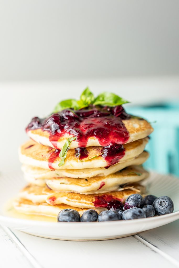 side view of pancakes with blueberry compote and basil leaves on top