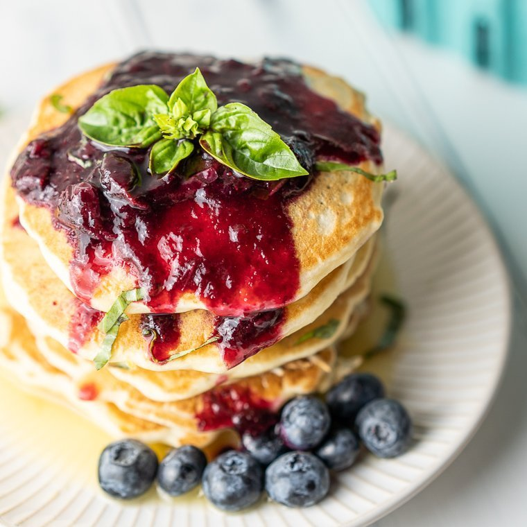 top view of pancakes with blueberry compote and basil leaves on top