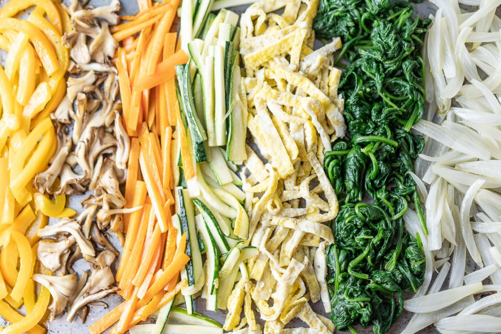a close up of a tray with all japchae vegetables lined up