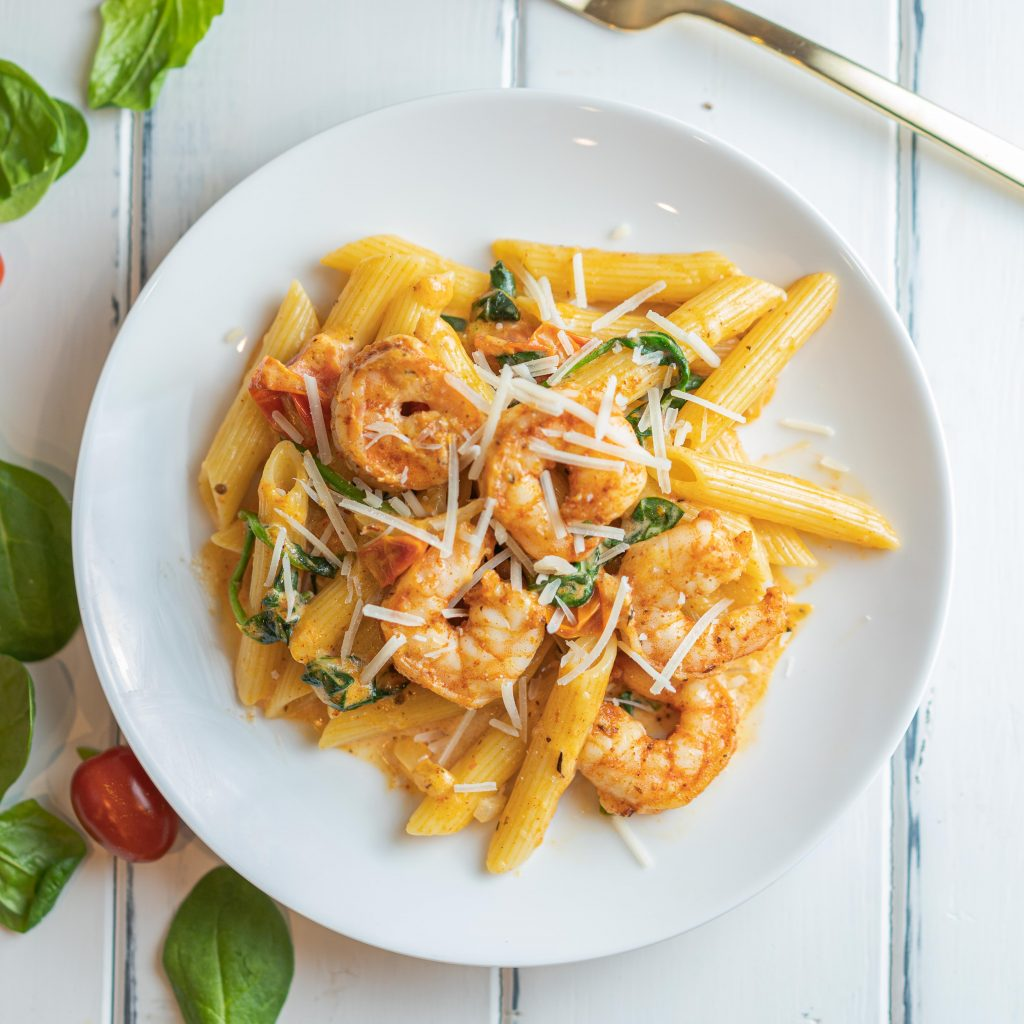 overhead shot of penne pasta topped with shrimp and cheese